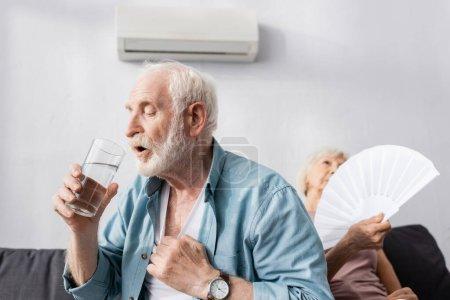 Photo pour Foyer sélectif de l'homme âgé tenant verre d'eau près de la femme avec ventilateur sur le canapé - image libre de droit