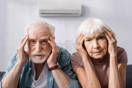 Pareja mayor mirando a la cámara mientras sufre de calor en casa