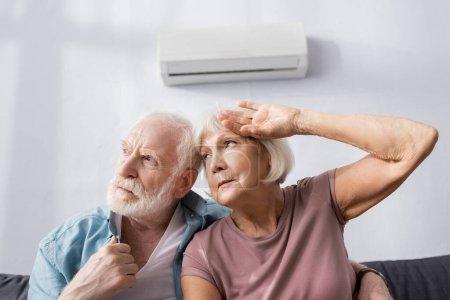 Photo pour Fatigué couple âgé regardant loin tout en se sentant chaud sur le canapé sous climatiseur - image libre de droit