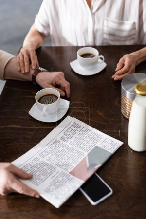 Cropped view of elderly couple sitting near cups of coffee, smartphone and newspaper on table