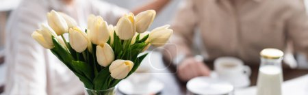 Photo for Panoramic crop of tulips in vase and senior couple drinking coffee at background - Royalty Free Image