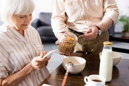Selective focus of senior woman using smartphone near husband holding jar of cereals at home