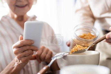 Photo pour Concentration sélective de la femme âgée en utilisant un smartphone pendant que le mari verse des céréales dans un bol - image libre de droit