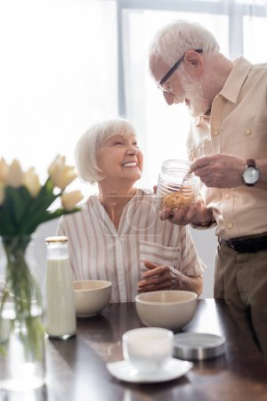 Photo for Selective focus of senior couple smiling at each other during breakfast in kitchen - Royalty Free Image