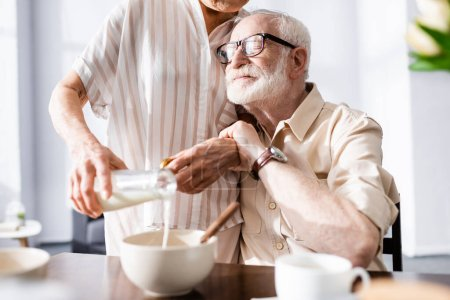 Selective focus of senior man embracing wife pouring milk in bowl during breakfast