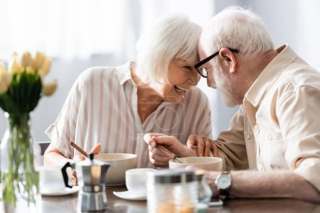 Photo for Selective focus of positive senor couple looking at each other near coffee and breakfast on table - Royalty Free Image