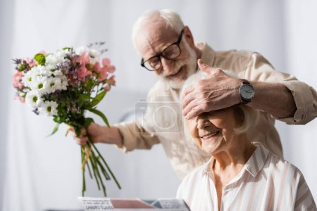 Photo for Selective focus of smiling senior man covering eyes of wife and holding bouquet - Royalty Free Image