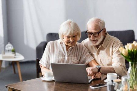 Photo pour Concentration sélective de sourire couple âgé en utilisant un ordinateur portable près des tasses à café sur la table - image libre de droit