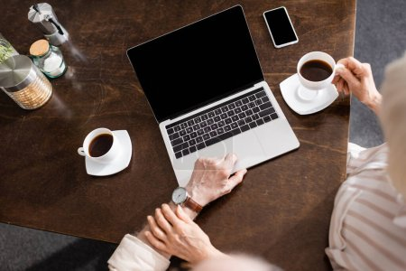 Photo for Overhead view of senior woman touching husband using laptop near coffee and smartphone on table - Royalty Free Image