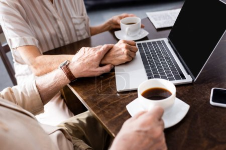Cropped view of elderly man touching hand  of wife near cups of coffee and digital devices on table