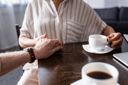 Photo for Cropped view of senor couple holding hands while drinking coffee at table - Royalty Free Image