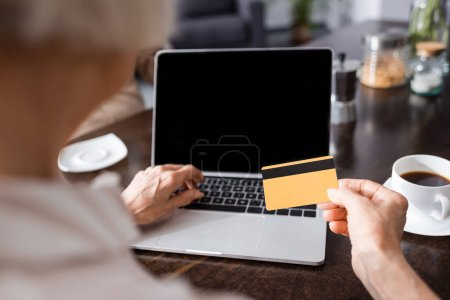 Selective focus of elderly woman using credit card and laptop near cup of coffee on kitchen table