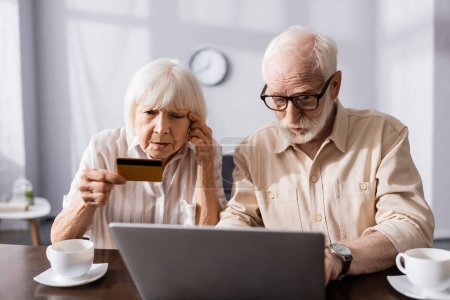 Photo for Selective focus of senior woman looking at credit card near man using laptop and cups on table - Royalty Free Image