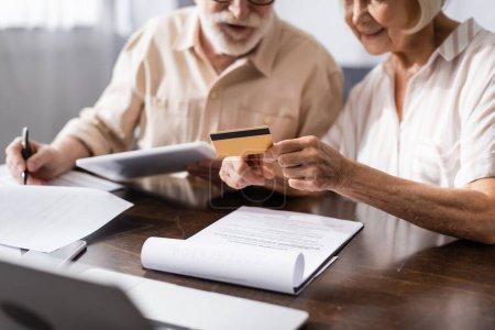 Photo pour Concentration sélective de la femme âgée tenant la carte de crédit tandis que le mari écrit sur les papiers près des gadgets sur la table - image libre de droit