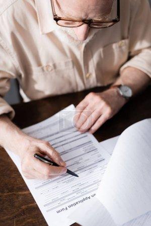 Photo pour Concentration sélective de l'homme âgé en lunettes écrivant sur des papiers à table - image libre de droit