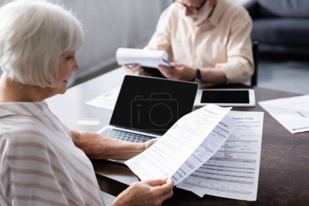 Photo for Selective focus of smiling senior woman holding papers near gadgets and credit card on table - Royalty Free Image