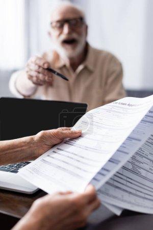 Photo pour Concentration sélective de la femme tenant des documents près de l'ordinateur portable et le mari pointant avec un stylo à la maison - image libre de droit