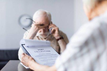 Selektiver Fokus der Frau, die Dokumente mit Inkasso-Schriftzug in der Hand hält, während ihr trauriger Ehemann auf dem Smartphone spricht
