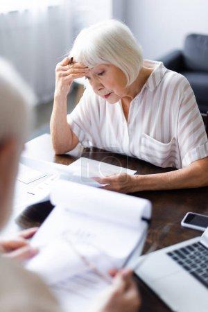 Photo pour Concentration sélective de femme âgée bouleversée tenant un stylo et regardant les papiers près du mari et des gadgets à la maison - image libre de droit