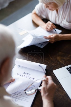 Photo for Selective focus of elderly couple looking at papers with debt collection near laptop on table - Royalty Free Image
