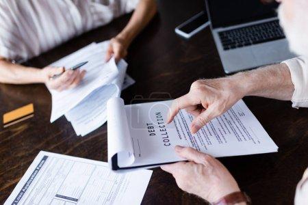 Photo pour Vue recadrée de l'homme âgé pointant vers le papier avec lettrage de recouvrement de créances près des gadgets et de la femme à la maison - image libre de droit