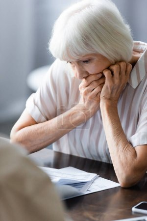 Photo for Selective focus of worried senior woman looking at papers on table - Royalty Free Image