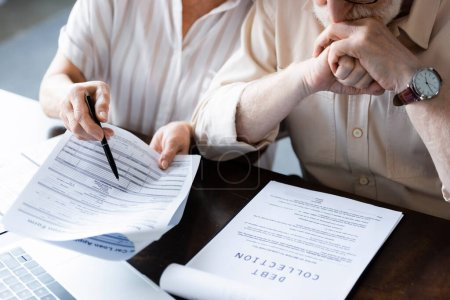 Photo for Cropped view of senior woman pointing at papers near husband and document with debt collection lettering on table - Royalty Free Image