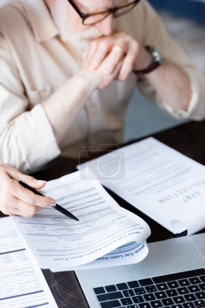 Photo for Selective focus of woman pointing with pen near papers and laptop beside upset senior man - Royalty Free Image