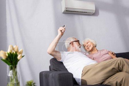 Photo pour Foyer sélectif de l'homme souriant commutation climatiseur avec télécommande près de la femme - image libre de droit