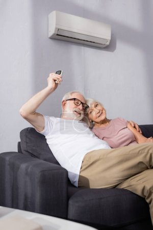 Photo for Selective focus of smiling elderly man embracing wife and using remote controller of air conditioner at home - Royalty Free Image