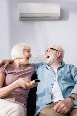 Selektiver Fokus des lachenden älteren Mannes, der seine Frau mit der Fernbedienung der Klimaanlage umarmt