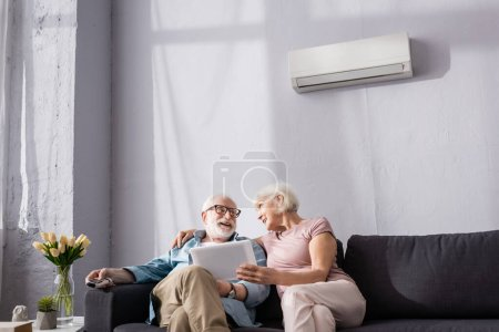 Photo for Senior woman holding digital tablet and looking at smiling husband holding remote controller of air conditioner at home - Royalty Free Image