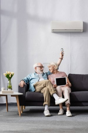 Photo for Smiling senior couple holding digital tablet and remote controller of air conditioner at home - Royalty Free Image