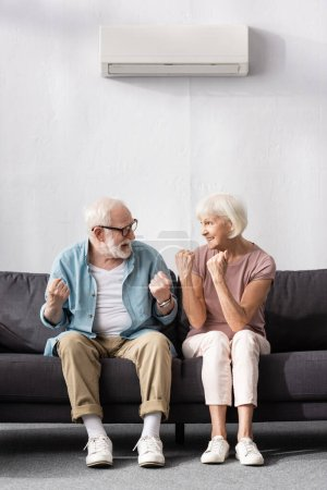 Photo for Smiling senior couple looking at each other and showing yeah gesture at home - Royalty Free Image