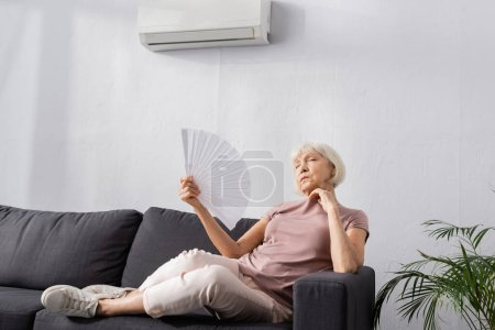 Photo pour Concentration sélective de la femme âgée agitant ventilateur tout en étant assis sur le canapé dans le salon - image libre de droit