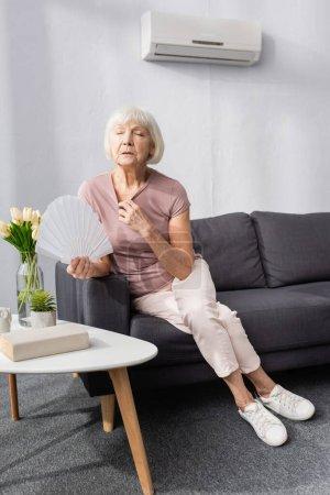 Photo pour Concentration sélective de la femme âgée tenant ventilateur tout en sentant la chaleur dans le salon - image libre de droit