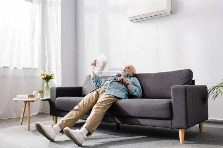 Photo pour Homme âgé fatigué tenant le journal sur le canapé sous climatiseur à la maison - image libre de droit