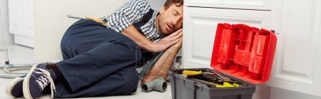 Panoramic shot of plumber sleeping near pipes and toolbox in kitchen