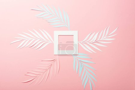 Photo for Top view of white, pink and blue paper cut palm leaves and square frame on pink background - Royalty Free Image