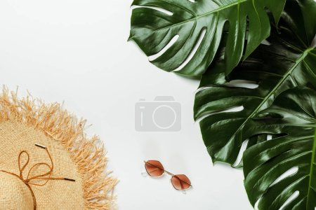 Photo for Top view of green palm leaves, straw hat and sunglasses on white background - Royalty Free Image