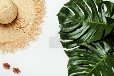 Photo pour Vue du dessus des feuilles de palmier vert, chapeau de paille, lunettes de soleil sur fond blanc - image libre de droit