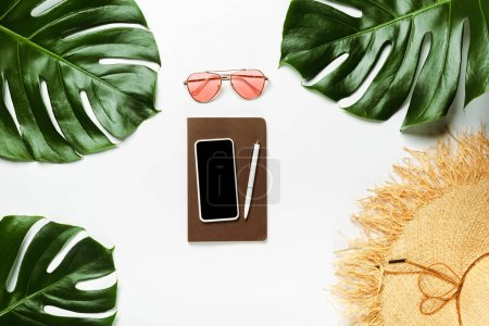 Photo for Top view of green palm leaves, straw hat, sunglasses and notepad with smartphone on white background - Royalty Free Image