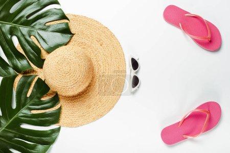 Photo pour Vue du dessus des feuilles de palmier vert, chapeau de paille, lunettes de soleil et tongs sur fond blanc - image libre de droit