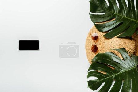 Photo pour Vue du dessus des feuilles de palmier vert, chapeau de paille, lunettes de soleil et bloc-notes avec smartphone sur fond blanc - image libre de droit