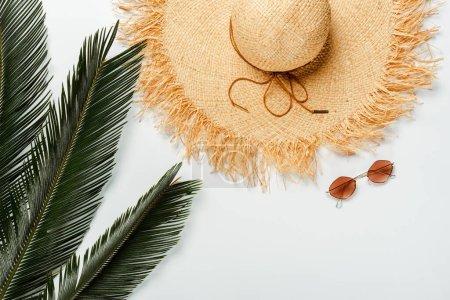 Photo pour Vue du dessus des feuilles de palmier vert, chapeau de paille et lunettes de soleil sur fond blanc - image libre de droit