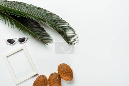 Photo pour Vue de dessus des feuilles de palmier vert, lunettes de soleil, noix de coco et cadre carré sur fond blanc - image libre de droit