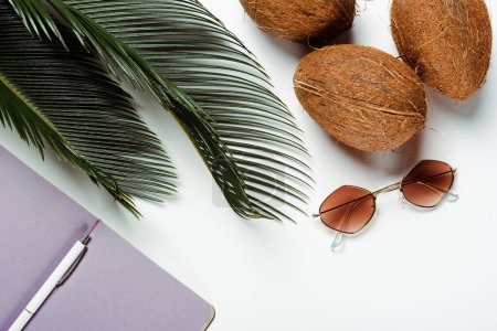 Photo for Top view of green palm leaves, sunglasses, coconuts and notepad on white background - Royalty Free Image