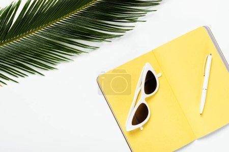Draufsicht auf grünes Palmblatt neben Sonnenbrille auf gelbem Planer auf weißem Hintergrund