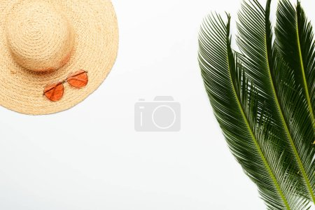 top view of green palm leaves near straw hat and sunglasses on white background