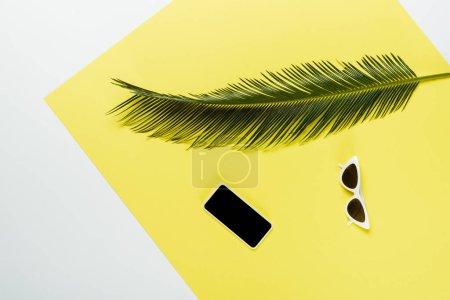 Photo pour Vue du dessus de la feuille de palme verte près des lunettes de soleil et smartphone sur fond blanc et jaune - image libre de droit